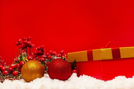 Gift and Christmas ball on snow on a red background