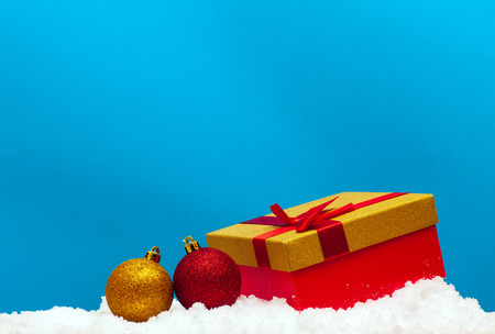 Gift and Christmas ball on snow on a blue background
