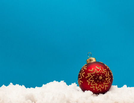 Christmas ball on snow on blue background