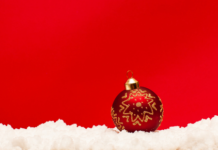 Christmas ball on snow on red background Stock Photo