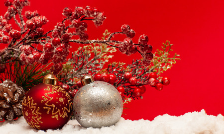 Christmas balls on the snow on a red background