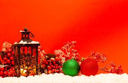 Lanterna della candela e palle di natale su neve su fondo rosso Archivio Fotografico
