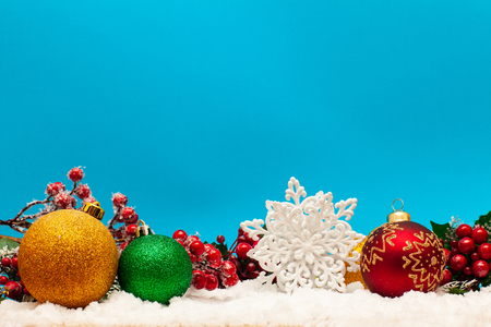 Christmas balls on the snow on a blue background