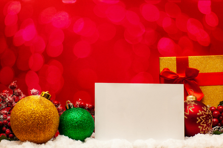 Christmas balls, note and gift on red background