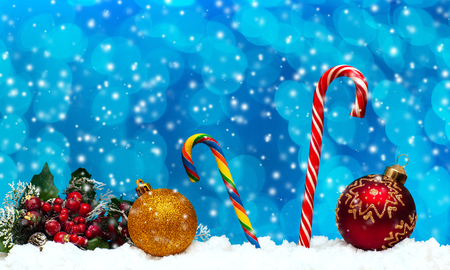 Caramel sweets and Christmas balls in the snow