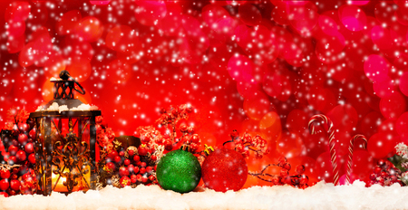 Candle lantern and christmas balls on snow on red background Stock Photo
