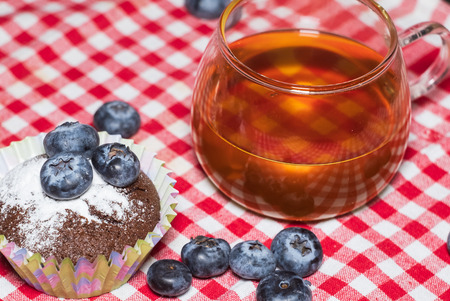 Cup of hot tea and muffins with blueberries on the table