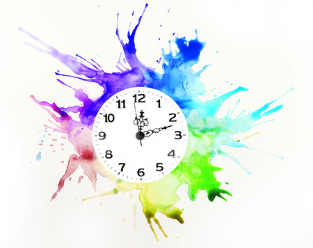 Clock and multicolor spilled paint on white background
