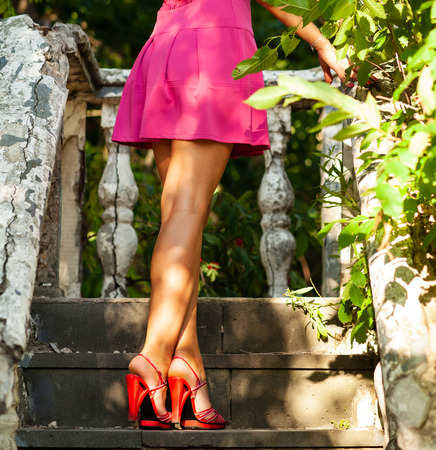 Beautiful slender female legs in sandals on the stairs