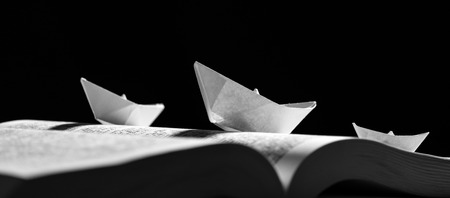Paper boats on the opened book on a black background