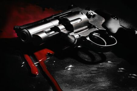 Beautiful revolver and red blood on a black