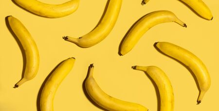 Ripe yellow bananas on a yellow background