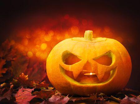 Hermosa calabaza de halloween tallada sobre un fondo naranja con bokeh