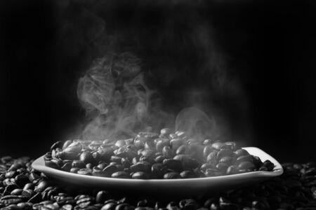 roasted steaming coffee beans in a saucer on a black background