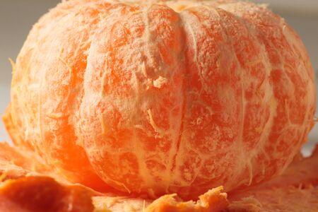 photo of ripe close-up beautiful ripe orange mandarin peeled