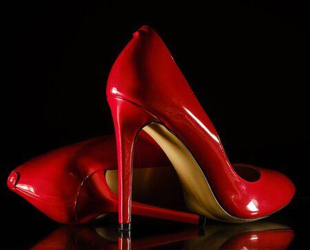 beautiful patent leather shiny female red stilettos on a black background 版權商用圖片