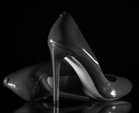 beautiful patent leather shiny female gray stilettos on a black background