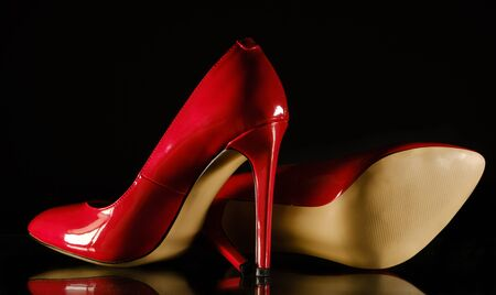 beautiful patent leather shiny female red stilettos on a black background 版權商用圖片 - 139331336