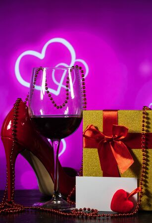 glass of wine and a wrapped gift and shoes on a table on a background with hearts and a note