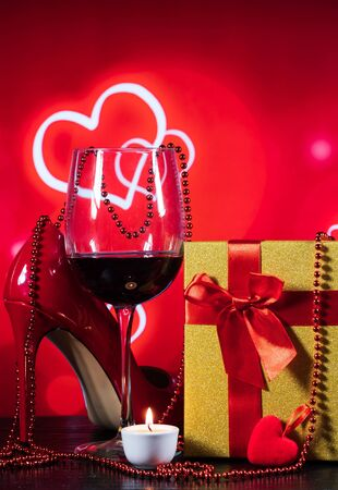 glass of wine and a wrapped gift and red shoes on a table on a red background with hearts and a candle