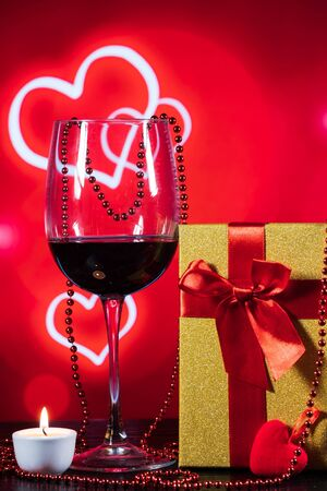 glass of wine and a wrapped gift on a table on a red background with hearts and a candle 版權商用圖片