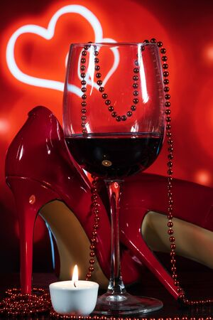 glass with wine, red beautiful shoes and a candle on a red background with hearts