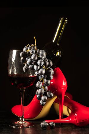 wine glass with grapes and red shoes on a black background  版權商用圖片