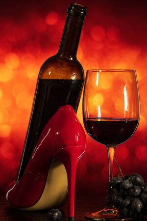 wine glass with grapes and red shoes on an orange background with bokeh 版權商用圖片 - 139926387