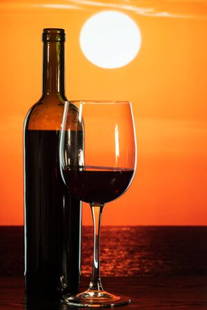 bottle and a glass of wine on the table against the backdrop of a beautiful orange sunset