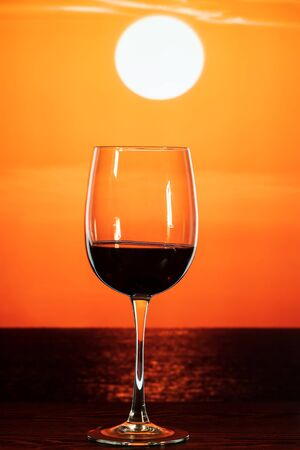 glass of wine on the table against the backdrop of a beautiful orange sunset
