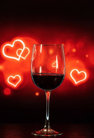 glass of wine on a table on a beautiful black-red background with hearts