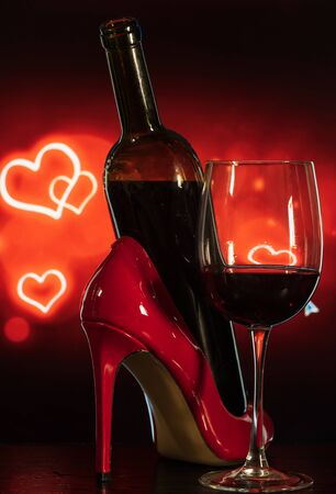 glass of wine and red shoes on a table on a beautiful black-red background with hearts