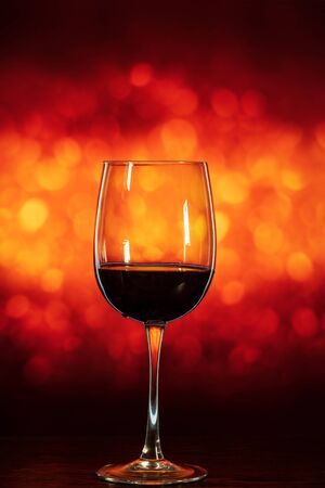 glass of wine on the table on an beautiful orange background with bokeh