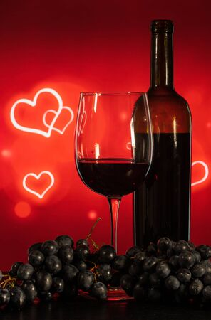 glass with wine and grapes on a table on a red background with hearts