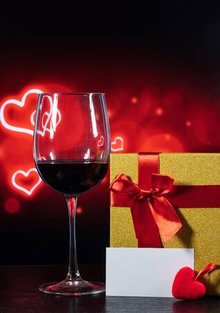 glass of wine and a wrapped gift on a table on a background with hearts and a note