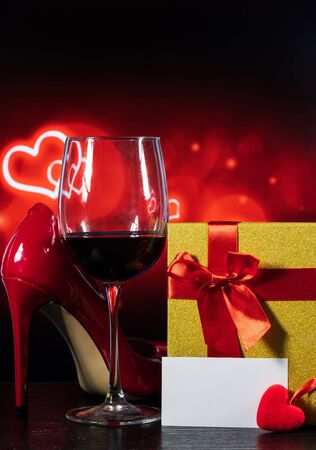glass of wine and a wrapped gift and red shoes on a table on a background with hearts and a note