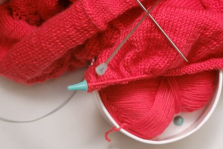 knitting a warm sweater and red wool yarn