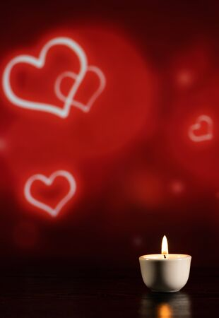 small candle on the table on a beautiful red background with hearts