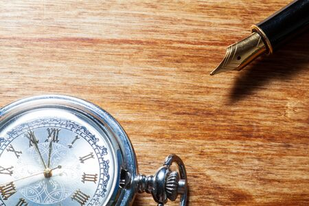 golden fountain pen and pocket watch on a wooden table Standard-Bild
