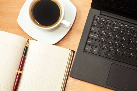 opened laptop, opened diary and coffee on an office wooden table