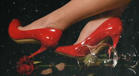 female feet in beautiful red high-heeled shoes and a glass with a rose on a black background