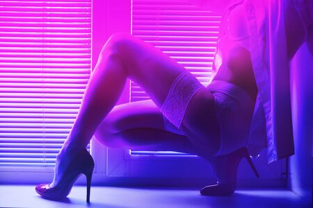 beautiful female legs in stockings and high-heeled shoes on the windowsill by the window with shutters in neon lighting