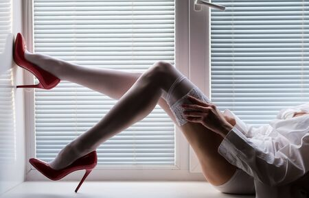 beautiful long female legs in white stockings and red high-heeled shoes on a window sill by the window with shutters