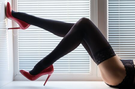 beautiful long female legs in black stockings and red high-heeled shoes on a window sill by the window with shutters Stock Photo