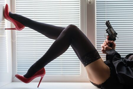 beautiful long legs in black stockings and red shoes and a revolver in hands on a window sill by the window with shutters