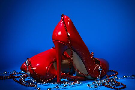 beautiful patent leather shiny female red stilettos and beads on a blue background