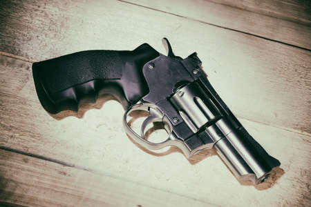 chrome revolver lies on a wooden table