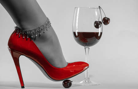 female feet with chain decoration in patent leather shiny red stiletto heels and wine glass
