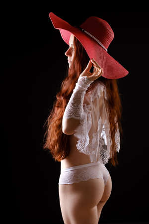 beautiful woman in white lingerie and with long red hair in a big hat on black Standard-Bild