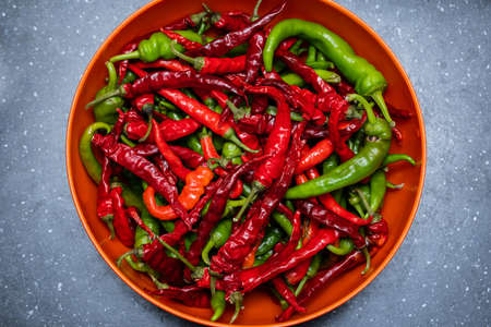 red and green hot chili peppers in a bowl on the table